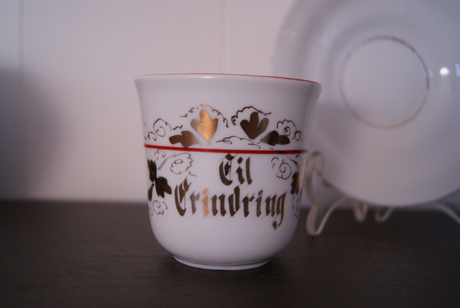 "Porsgrund cup with saucer, golden decor, red band and inscription: ""til erindring"""
